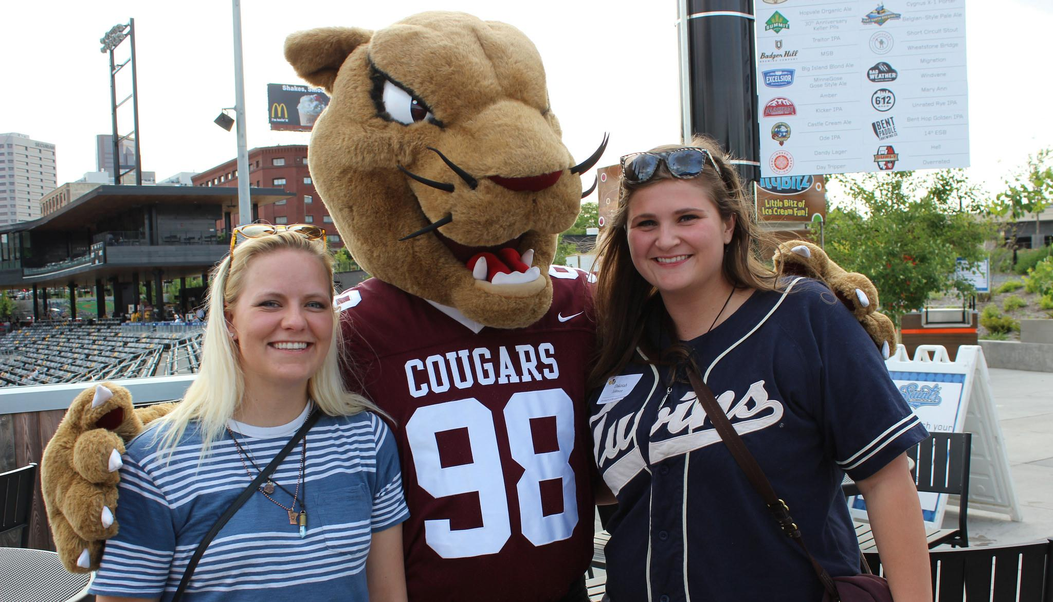 Alumni posing with Pounce at the Saints baseball game.