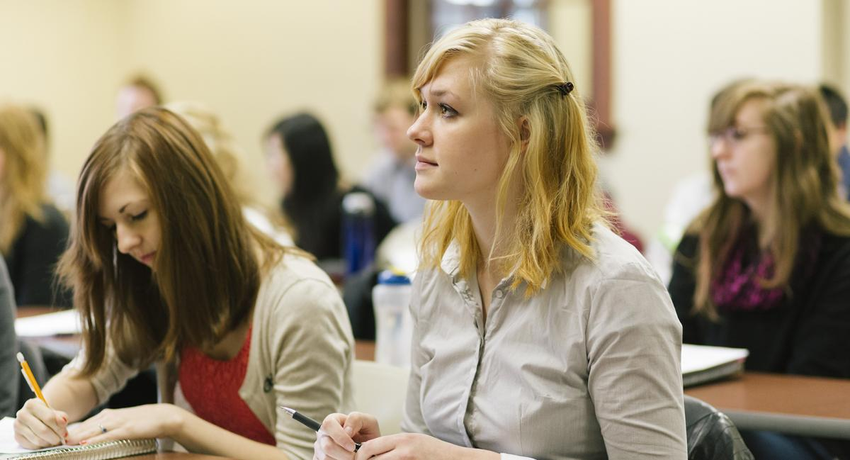 A young woman in a classroom looking up thoughtfully