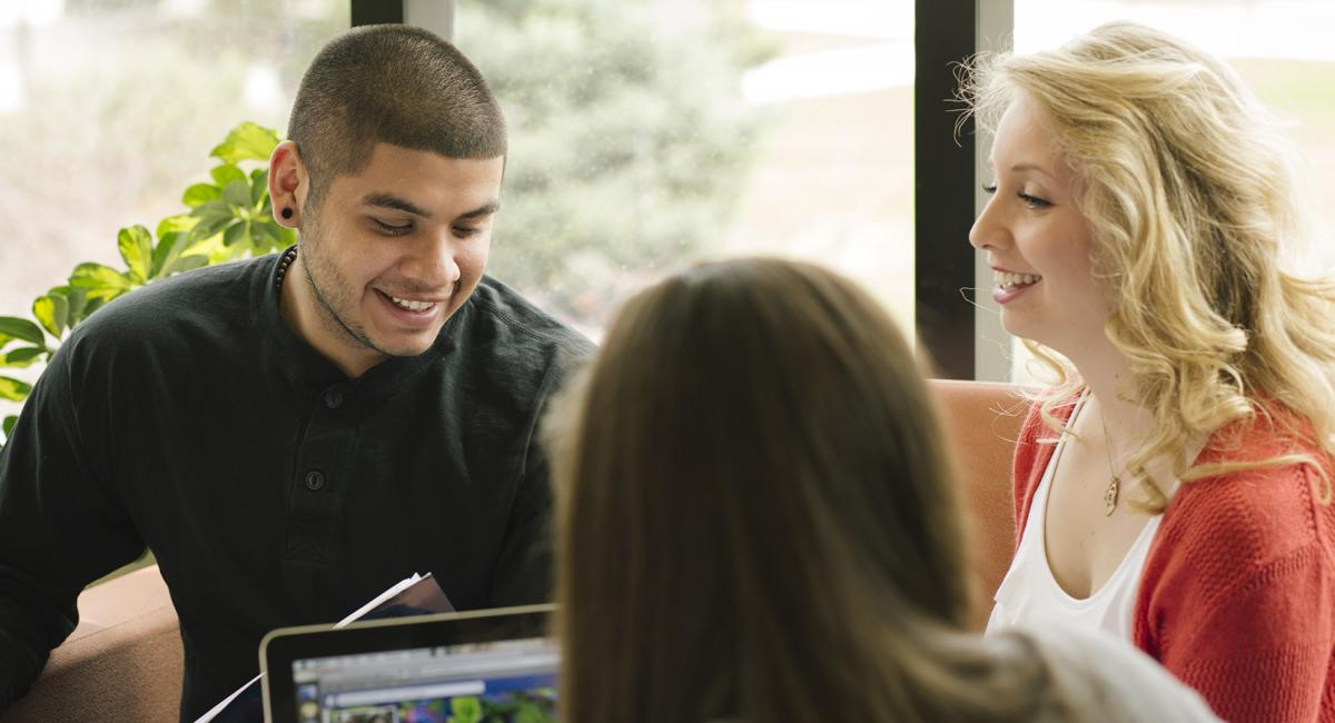 A smiling young man and a smiling young woman looking at books and an open laptop