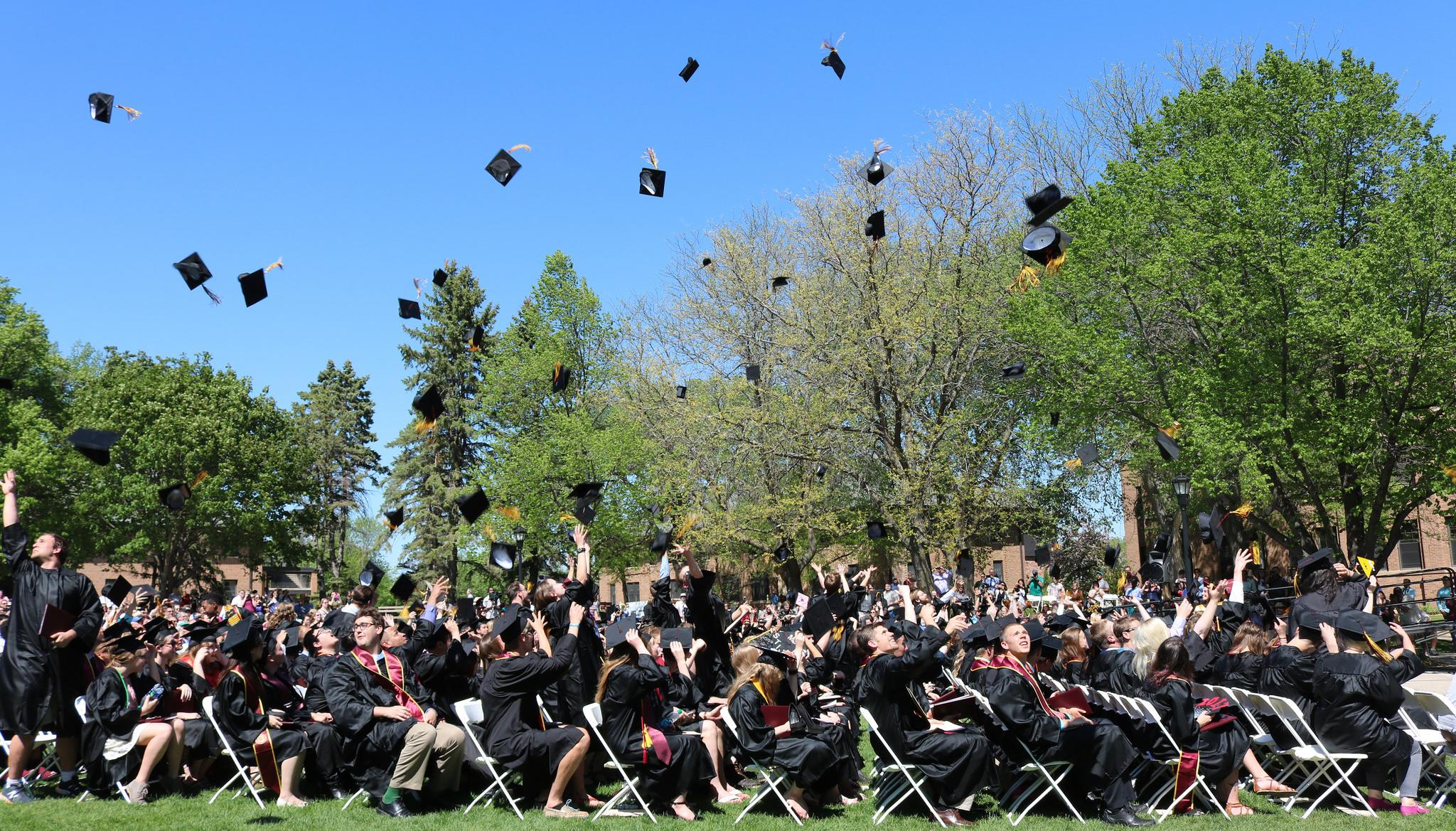 Morris graduates throwing caps in the air at Commencement