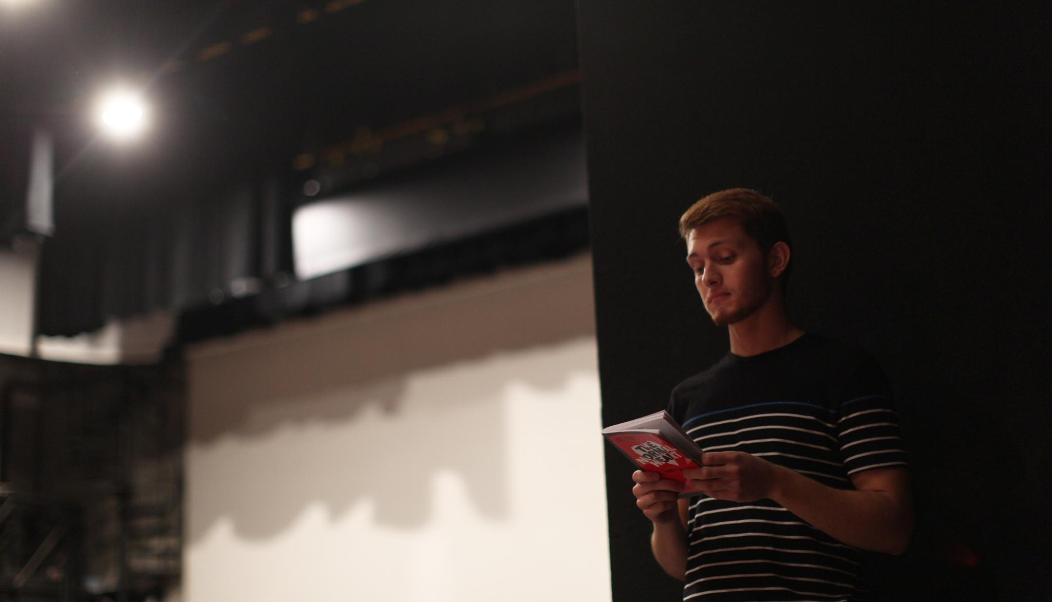 A young man standing backstage at a theatre and holding a script