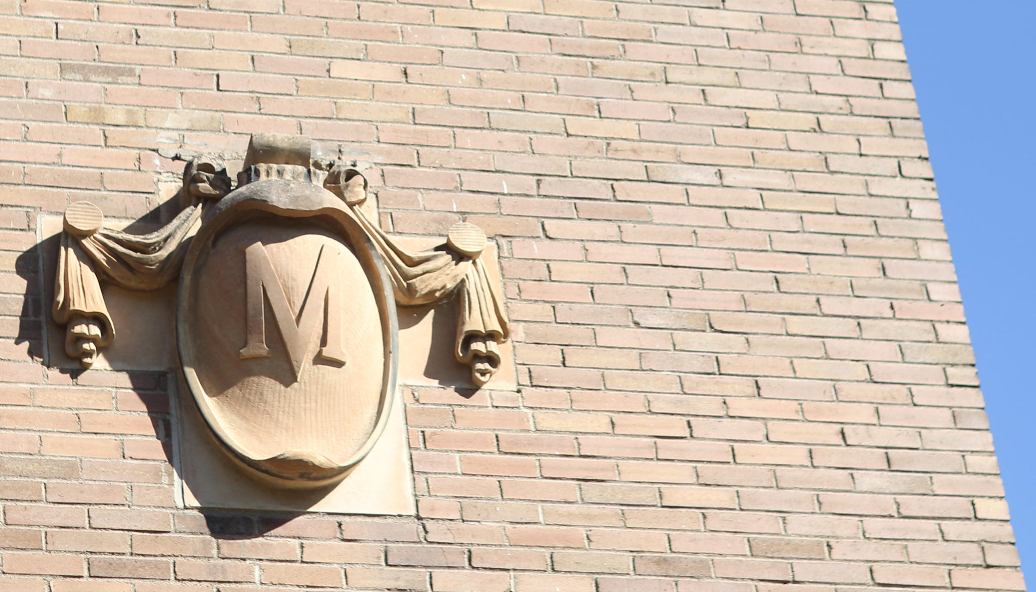 A stylized M on the side of a brick building, blue sky in the background