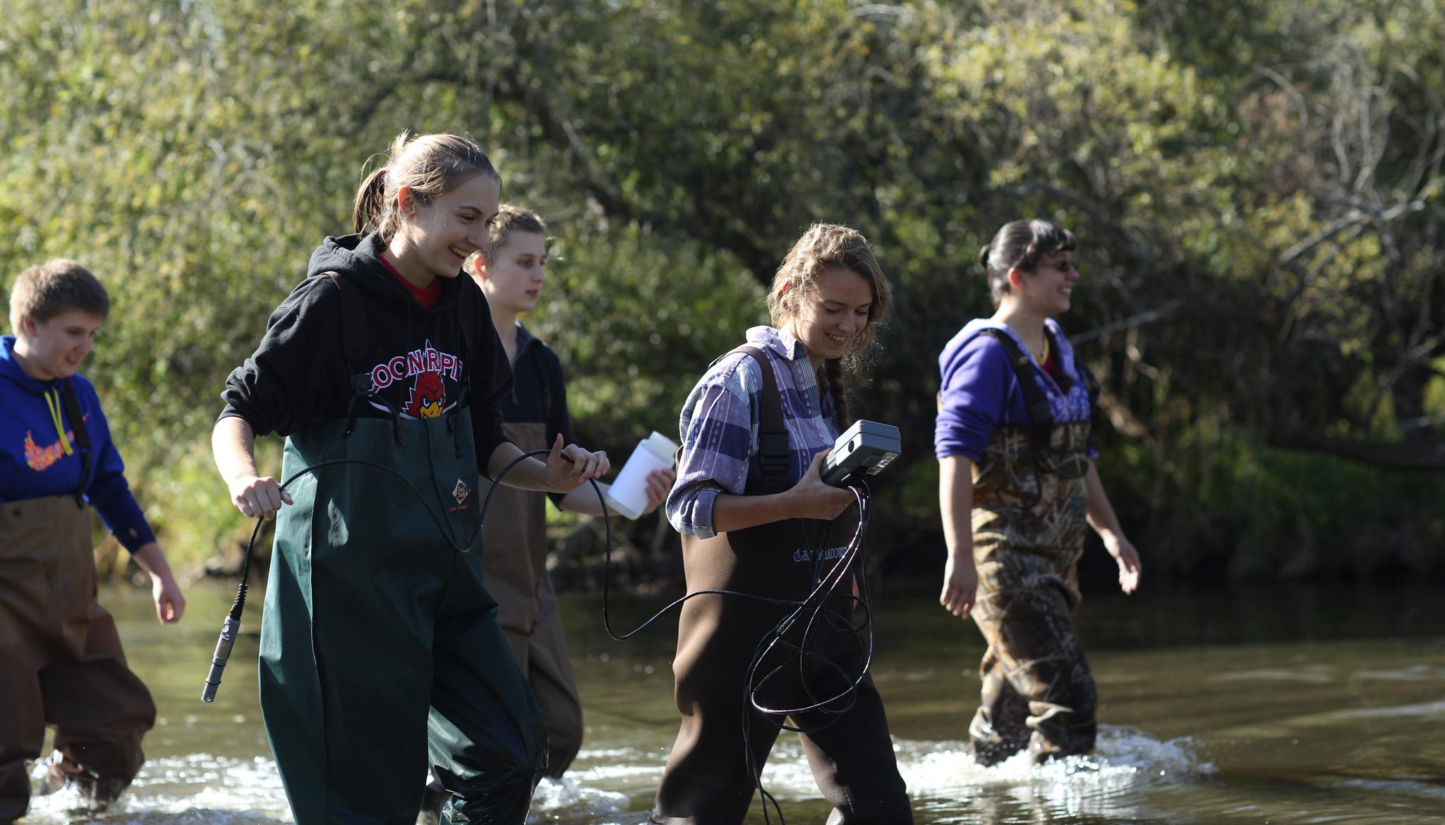Students wearing waders walking in a stream