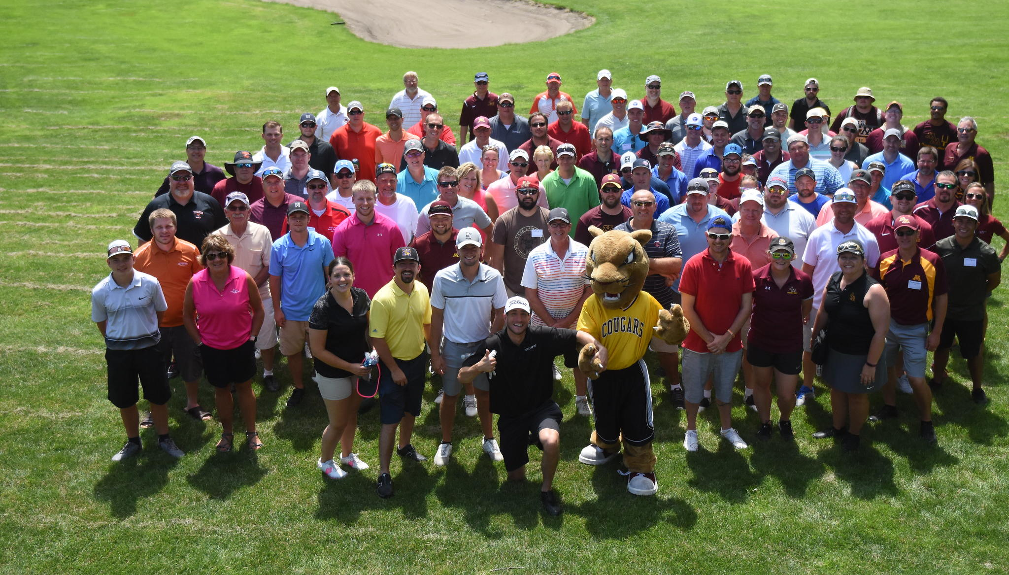 UMN Morris alumni and friends golfing with Pounce the Cougar