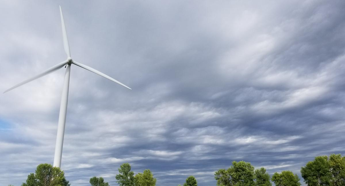A wind turbine against a gray-blue sky on a partly cloudy fall day