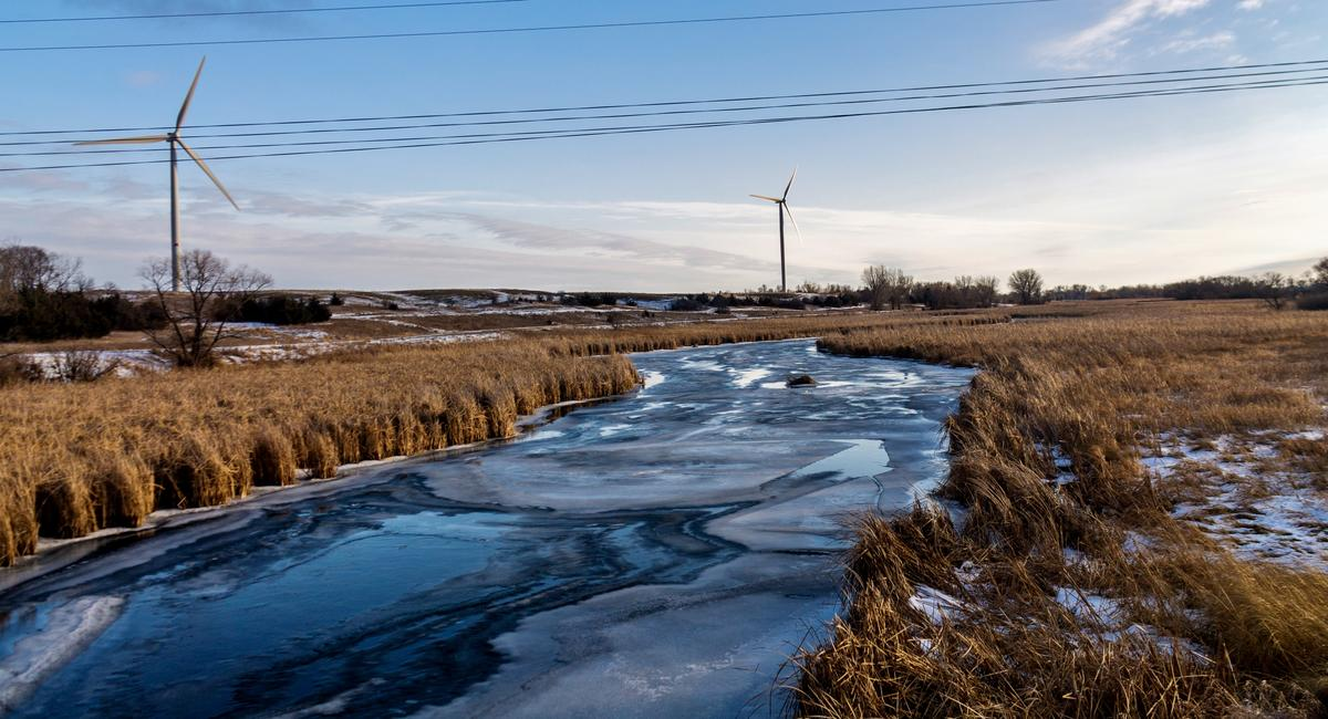 Two wind turbines next to a frozen river