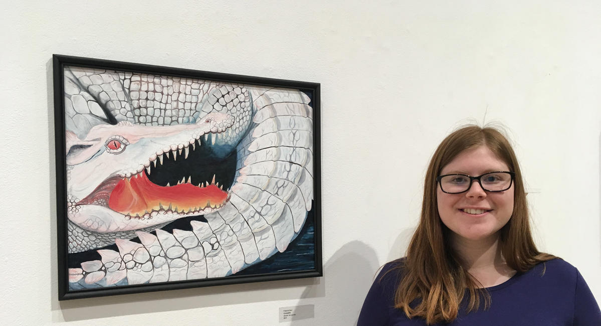 "Frances Burr '18 stands next to her ""Crocodile"" artwork in a gallery"