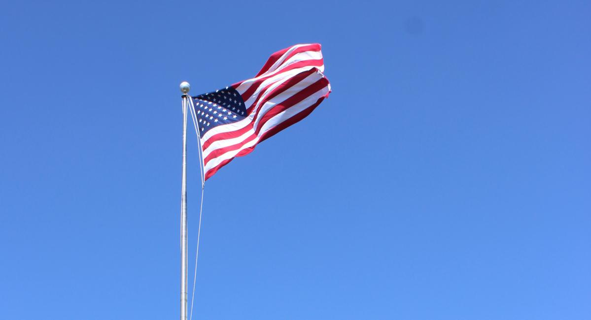 An American flag waving against a bright blue sky