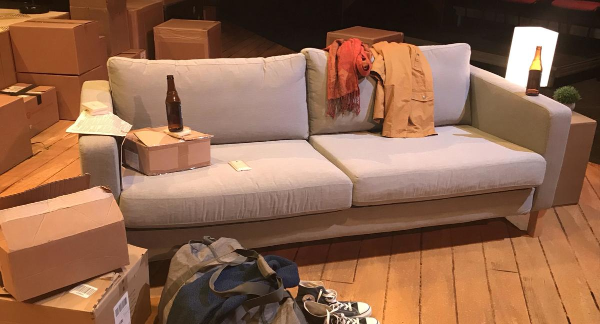 A prop couch on a theatre set; cardboard boxes are stacked in the background