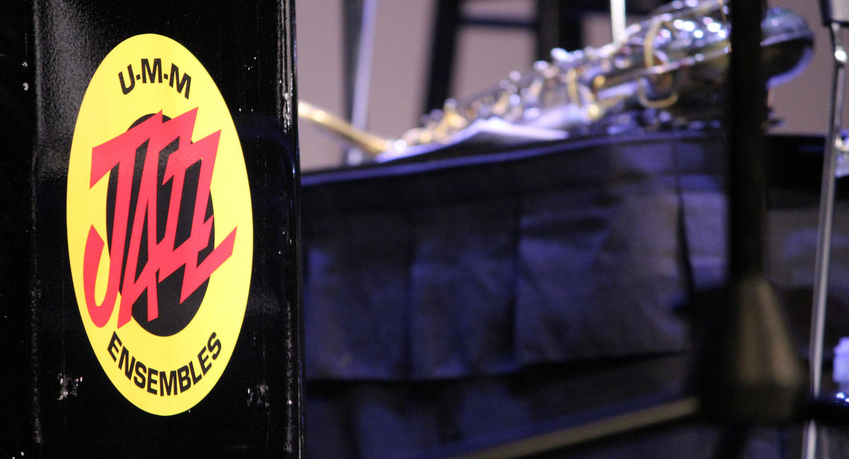 UMM Jazz Fest logo on a drum in the foreground, stage set up in the background