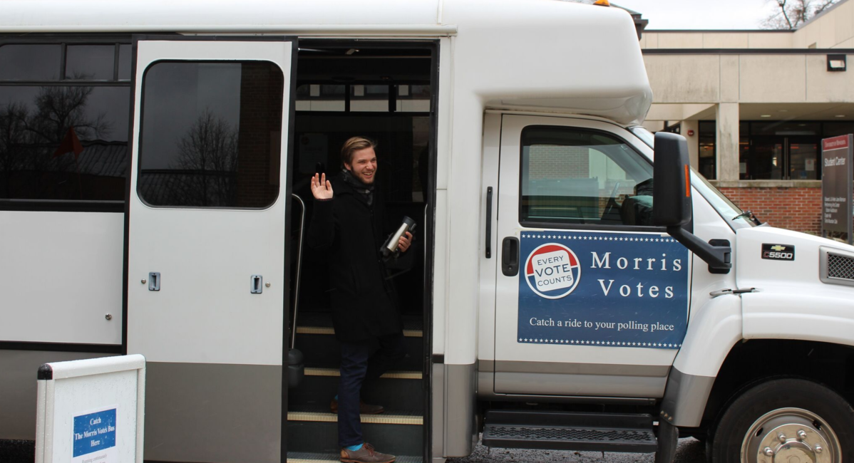 """A UMN Morris student boards a bus with a """"Morris Votes"""" sticker on the side"""