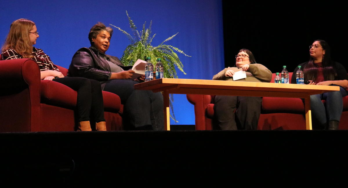 Four women seated on couches on a stage, having a conversation