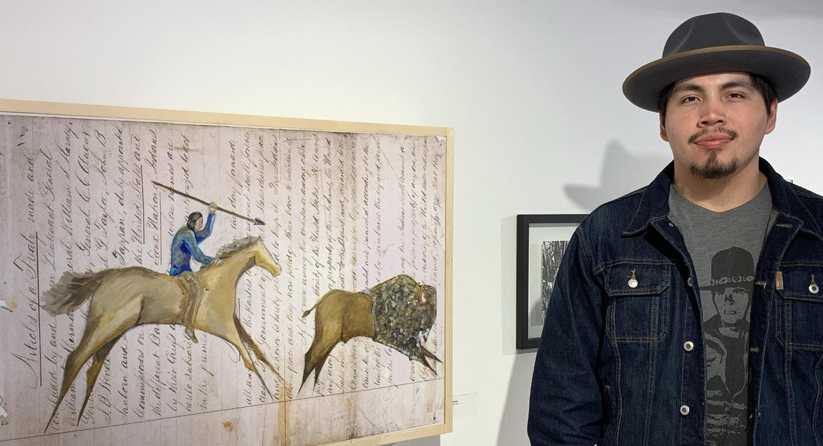 Bray Benoist standing next to his ledger art-inspired work The Last Hunt