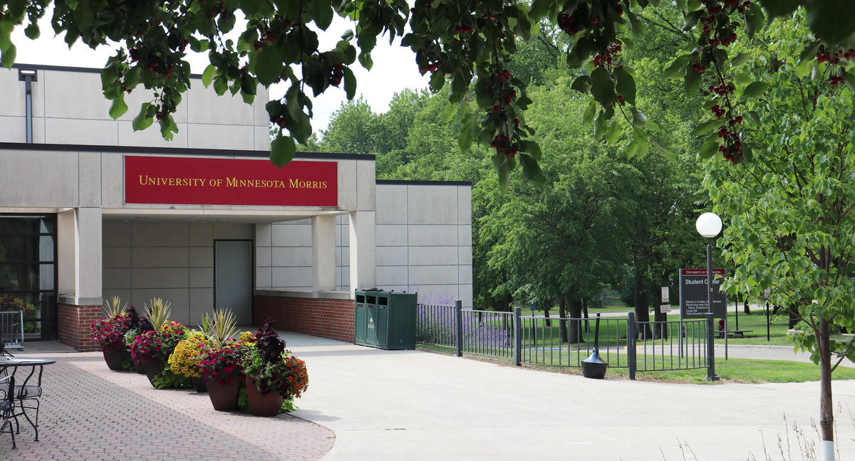 "The entrance to the UMN Morris Student Center on a sunny summer day, with a maroon sign reading ""University of Minnesota Morris"" hanging over the entrance doors"