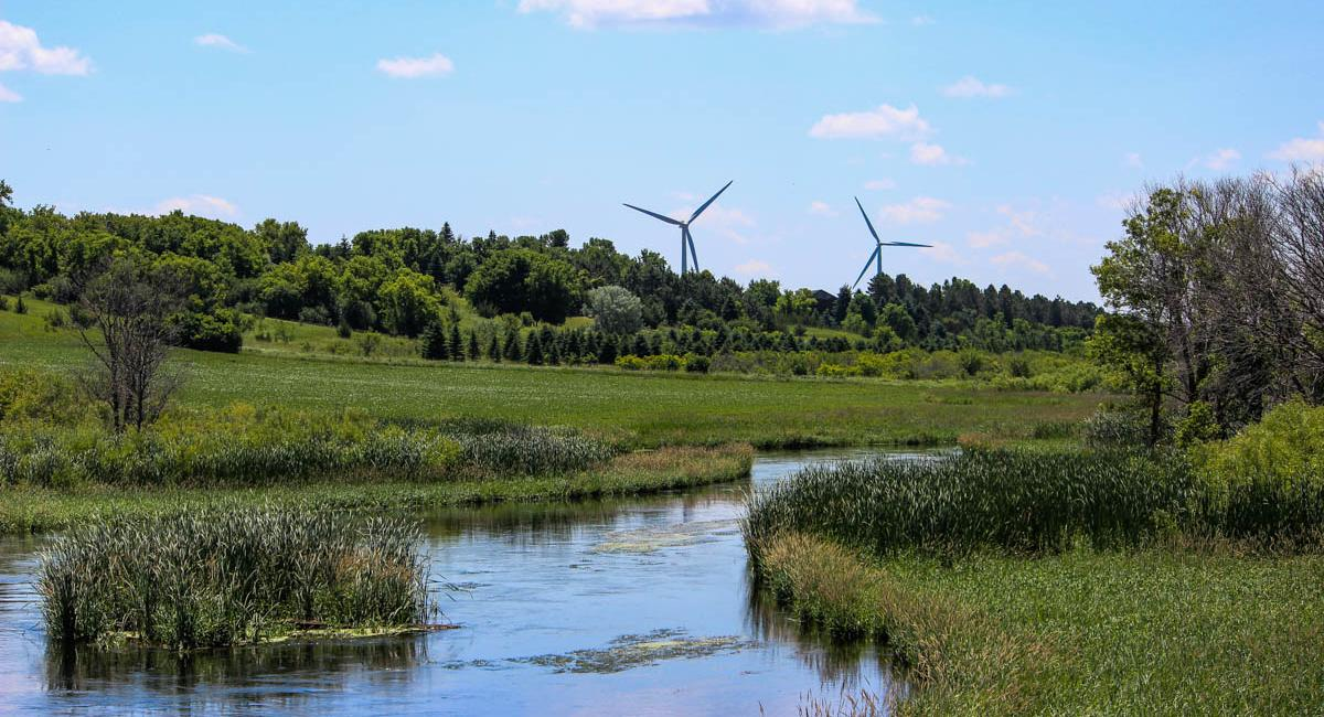 Two wind turbines overlooking a river