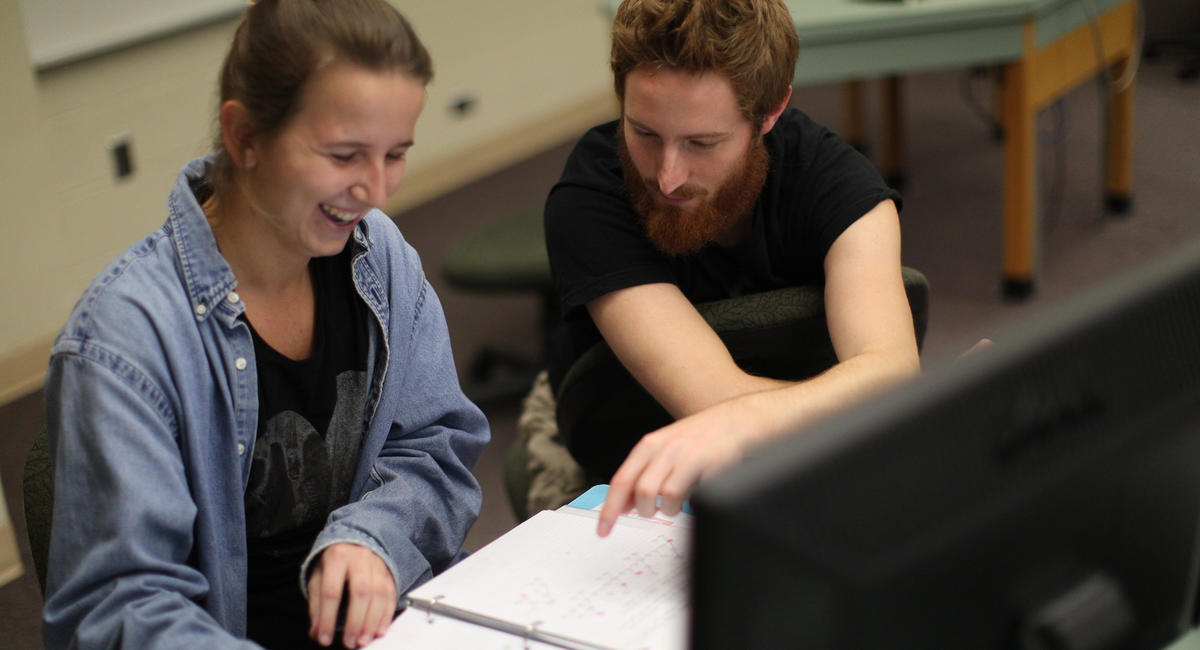 Two students working near a computer