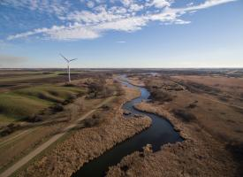 An aerial view of a wind turbine and the Pomme de Terre River