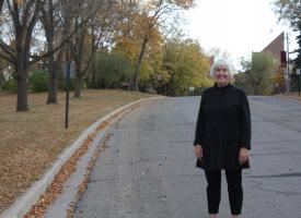 A smiling woman standing on a roadway