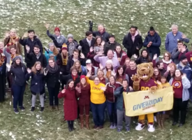 UMN Morris students, faculty, and staff standing on a grassy space with Pounce the Cougar, smiling and waving