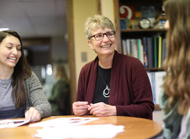 A candid photo of Sandra Olson-Loy sitting at a table with two students, smiling