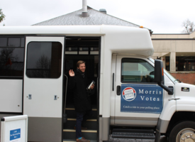 "A UMN Morris student boards a bus with a ""Morris Votes"" sticker on the side"
