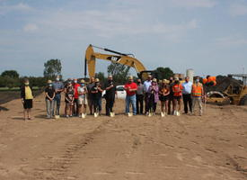 A group of city and school officials, wearing cloth face coverings, standing on a patch of dirt on a sunny summer day. Construction equipment and balloons in the school colors are seen in the background.