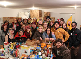 A group of students posing and smiling next to a large pile of canned goods and nonperishable food items