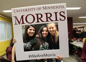 """Three students holding a """"WeAreMorris"""" photo prop"""