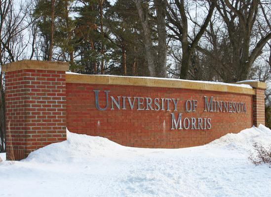 The UMN Morris 4th Street entrance sign, a brick facade with silver lettering reading University of Minnesota Morris, on a snowy day