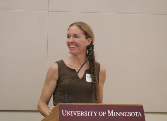 "Erika Bailey-Johnson standing at a podium, smiling. The podium reads ""University of Minnesota"""