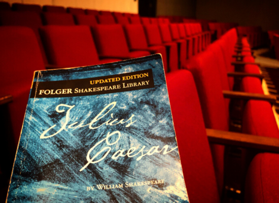 A blue playscript of Julius Caesar placed on a red velvet theater seat
