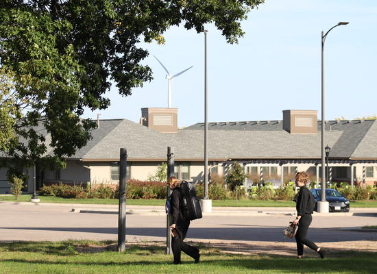 Students walking on the UMN Morris campus, Green Prairie Community and wind turbine in the background