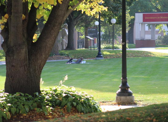 The UMN Morris Student Center and campus mall on a sunny fall day, at golden hour. A student lounges in the grass. A sculpture of an Indigenous woman is seen in the background.