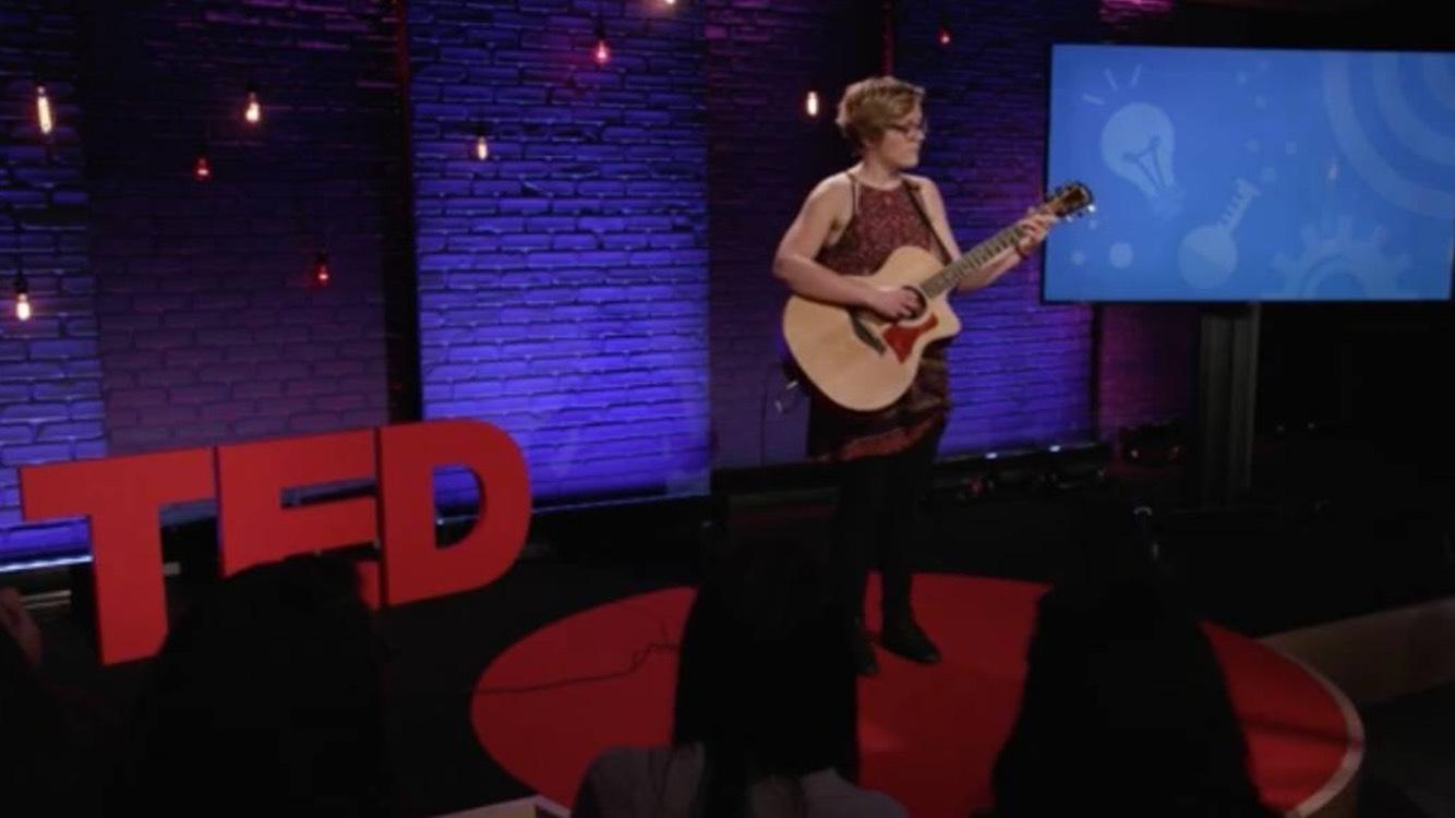 A young woman playing guitar onstage at TED
